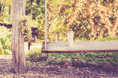 Wooden swing hanging in garden Stock Photos