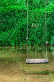 Wooden swing hanging on tree above the water stream at outside resort. Royalty Free Stock Photos