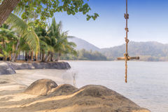 Wooden swing  hanging a tree on the tropical beach. - Selective f Stock Image
