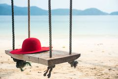 Wooden swing with a hat on tropical beach for summer and vacation. Royalty Free Stock Photo