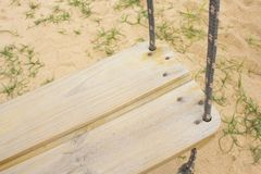 Wooden swing in the sand royalty free stock photo