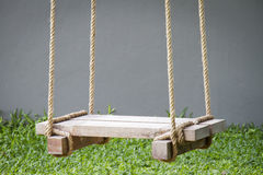 Wooden swing. With ropes on grass background Stock Photo