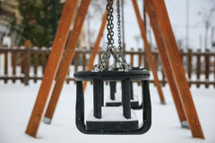 Wooden swing on snow Royalty Free Stock Image
