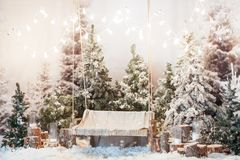 Wooden swing in a snow-covered park or forest with spruce trees and stumps, big candles in glass vases, while snowing Royalty Free Stock Photo