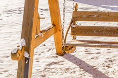 Wooden swing on a snow. Light brown wooden swing on a sunlit snow Royalty Free Stock Image