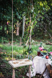 Wooden Swing with still life. Old wooden swing hanging from a tree decorated with leaves on green grass background near still life Stock Photos