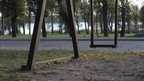 Wooden swing swinging at park. Someone has just gone and left the swings stock video
