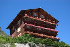 Wooden Swiss mountain chalet. Low angle view of traditional, wooden Swiss mountains chalet with colorful flower on balconies and blue sky background Royalty Free Stock Photos