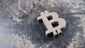 Wooden symbol of bitcoin falls to the dusty table stock footage