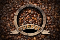 Wooden Symbol with Coffee Beans. Wooden round symbol or icon with roasted coffee beans inside and text Coffee. On a background with many coffee beans Royalty Free Stock Photos