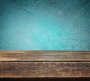 Wooden table against blue textured background Royalty Free Stock Image