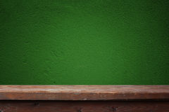 Wooden table against a green wall Royalty Free Stock Photos