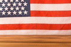 Wooden table and American flag in the background. Selective focus.  royalty free stock photography