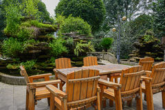 Wooden table and armchairs near rockery Royalty Free Stock Photo