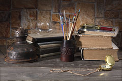 On the wooden table are: artist`s brushes, kerosene lamp, old books, magnifying glass and gold pocket watch. Stylized retro still Stock Images