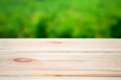 Wooden table on a background of bright green trees in the defocus. Perspective wood over blur trees with bokeh background, spring and summer season Royalty Free Stock Images