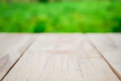Wooden table on a background of bright green trees in the defocus. Perspective wood over blur trees with bokeh background, spring and summer season Stock Photography