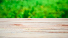 Wooden table on a background of bright green trees in the defocus. Perspective wood over blur trees with bokeh background, spring and summer season, the ratio of Stock Image