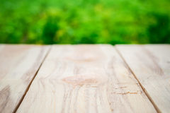 Wooden table on a background of bright green trees in the defocus. Perspective wood over blur trees with bokeh background, spring and summer season Royalty Free Stock Image