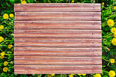 Wooden table on a background field of dandelions Royalty Free Stock Photography