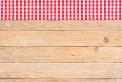Wooden table background with red checked fabric, top view. Tablecloth on wooden table, food background, red checked fabric, top view, copy space Royalty Free Stock Image