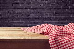 Wooden table background with red checked tablecloth over black brick wall Stock Images