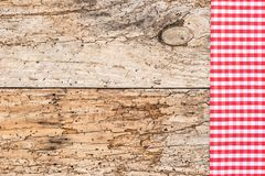 Wooden table background rustic texture, with red checkered tablecloth, high angel view. Vintage red checked napkin on old wood table background with copy space stock photo