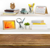 Wooden table on background of shelves with home related objects Royalty Free Stock Image
