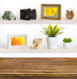 Wooden table on background of shelves with travel objects Royalty Free Stock Photography