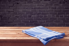 Wooden table background with tablecloth over black brick wall Stock Photo