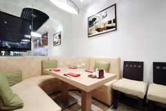 Wooden table, beige leather sofa in cozy restaurant Royalty Free Stock Image