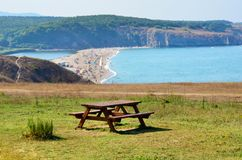 Wooden Table with Bench on a Beach with Blue Water and Green Meadow. Picnic Area on the beach - summer vacation background stock photo