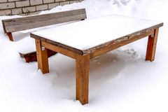 Wooden table and bench covered with snow royalty free stock photos