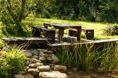 Wooden table bench in garden with stones and green fields Stock Image