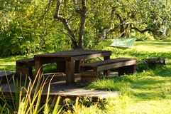 Wooden table bench hammock in garden Royalty Free Stock Images