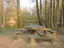 Wooden table and bench near lake Stock Photos