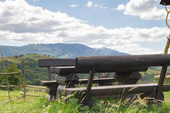 Wooden table and benches in the mountains Royalty Free Stock Photo