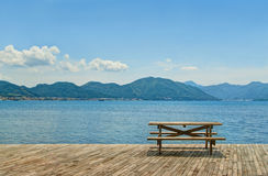 Wooden table and benches for picnic by sea. Wooden table and two benches for picnic standing on wooden flooring by sea on sunny day facing green mountainous Royalty Free Stock Photo