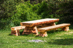 Wooden table with benches in a pine forest Royalty Free Stock Images