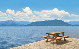 Wooden table with benches on platform at sea Royalty Free Stock Photo