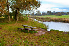 Wooden table and benches by river Royalty Free Stock Photography