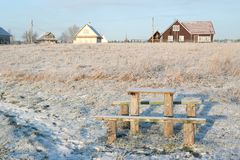 Wooden table and benches. The winter landscape. Snow-covered field, a wooden table and benches Stock Photos
