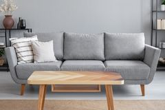 Wooden table and big grey couch with pillows in living room of trendy apartment, real photo royalty free stock photography