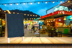 Wooden table and blackboard of night market. Empty wooden table and blackboard of night market Royalty Free Stock Images