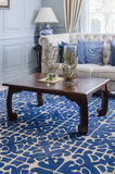 Wooden table on blue pattern carpet in luxury living room Stock Images
