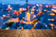 Wooden table with blur city night bokeh royalty free stock photography