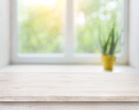 Wooden table on blurred autumn window with plant pot background.  Royalty Free Stock Image