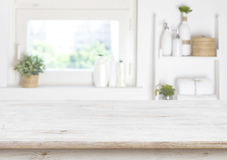 Wooden table on blurred background of bathroom window and shelves stock images