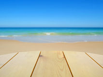 Wooden table on blurred beach royalty free stock image