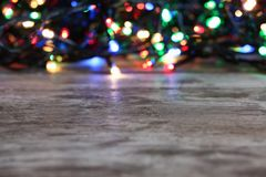 Wooden table and blurred Christmas lights royalty free stock photo